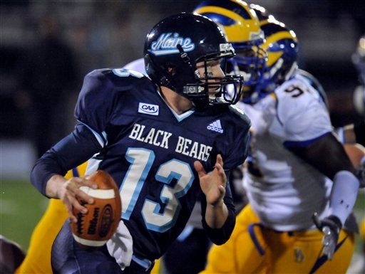 Maine's quarterback Warren Smith (13) scans the field for a potential pass while Delaware players close in during the first quarter of an  NCAA college football game Saturday, Oct. 3, 2009, in Orono, Maine. (AP Photo/Michael C. York)