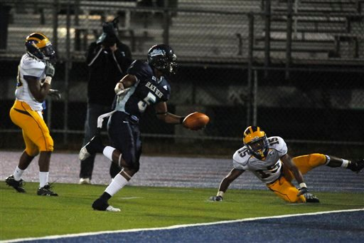 Maine's Desmond Randall (5) scores a touchdown after evading Delaware's defense in the first quarter of an NCAA college football game Saturday, Oct. 3, 2009, in Orono, Maine. (AP Photo/Michael C. York)