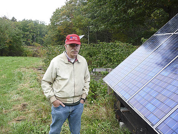 Rufus Wanning explains how his solar panels work Saturday during a green energy tour. Hundreds of homes and businesses in the Northeast that use alternative energy participated in the event, which was sponsored by the Northeast Alternative Energy Association. &quotI've never regretted the switch,'' Wanning said. &quotIt's not about not paying an electric bill,'' Wanning's wife, Margaret De Rivera said. &quotMy concern is the environment, global warming and reducing our carbon footprint.'' (Bangor Daily News/Sharon Kiley Mack)