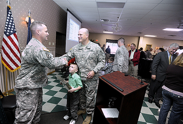 Master of Ceremony Maj. Jeffrey Bilodeau, left, congratulates Chief Warrant Officer Michael McGovern of Eddington after presenting his five-year-old son, Michael McGovern, center,  with an honorary footlocker following Sunday morning's Freedom Salute Presentation at the Spectacular Events Center in Bangor. The event honored McGovern and 11 other members of the Maine Army National Guard who have recently returned from deployment overseas as well as honoring several community supporters. (Bangor Daily News/John Clarke Russ)