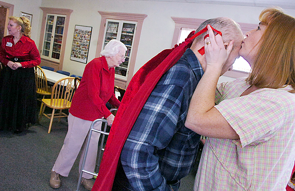 (BANGOR DAILY NEWS PHOTO BY KATE COLLINS)  CAPTION  Ronnie Joe Eddy, right, Assistant Resident Manager for the Sylvia Ross Home, kisses Oliver Doane as she helps him with his cape during the Valentine's Buffet and Dance held on Sunday, February 15, 2009.  Doane was crowned King of the event, with Mary Howard being chosen as Queen.  (Bangor Daily News/Kate Collins)