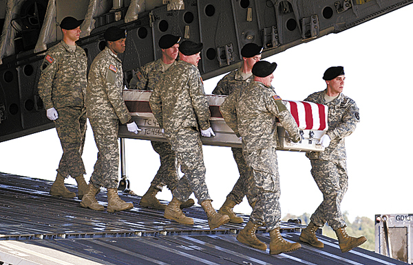 A carry team carries the transfer case containing the remains of Army Sgt. Joshua J. Kirk of South Portland, Maine, who died in Operation Enduring Freedom, Tuesday, Oct. 6, 2009, during the dignified transfer event at Dover Air Force Base in Dover, Del. (AP Photo/Susan Walsh)