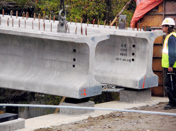 Two of the new beams rest on the abutment on the shore of the Orland River after they were set there on Friday. The beams will form the base of the concrete deck of the new bridge being constructed by crews from Lane Construction. 