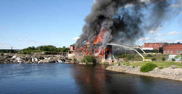 File - Flames shoot from the windows at the Cowan Mill at Island Point in downtown Lewiston, Maine in this July 16, 2009 file photo. The fire had fullyt engulfed the building by the time fire crews got to the scene around 4 p.m. A 13-year-old boy was arrested Thursday Oct. 8, 2009 in connection with the fire that destroyed the historic textile mill in Maine's second-largest city. (AP Photo/Justin Pelletier - Sun Journal, File)
