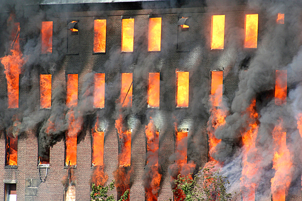 Flames shoot from the windows at the Cowan Mill at Island Point in downtown Lewiston, Maine on Wednesday, July 15, 2009. The fire had fully engulfed the building by the time fire crews got to the scene around 4. (AP Photo/Justin Pelletier, Sun Journal)