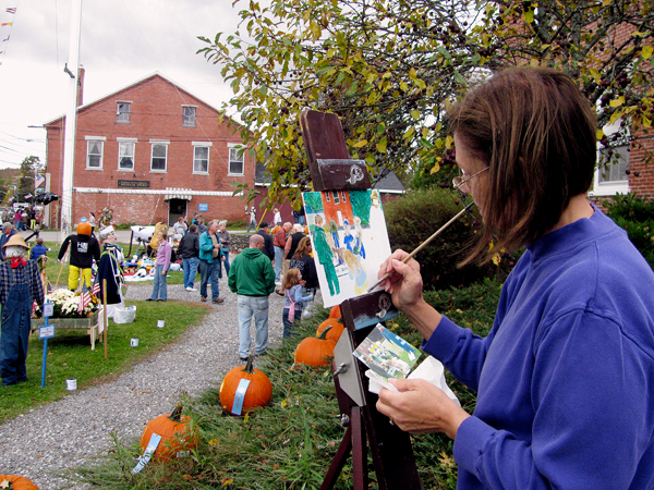 Artist Rainy Brooks of Searsport paints one of the scarecrows on display Saturday at Fling Into Fall. &quotI think it's great,&quot Brooks said of the seasonal festival. Her painting, along with the work of 24 other artists, was slated to be auctioned Saturday evening with at least half of the proceeds donated to the Penobscot Marine Museum. BANGOR DAILY NEWS PHOTO BY ABIGAIL CURTIS