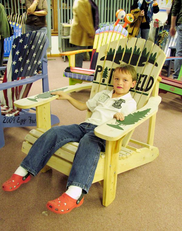 Johnny O'Brien, 6, of Pittsfield, tries out an Adirondack chair that he begged his parents to buy him Friday night during a fund raiser to benefit the Pittsfield Community Theatre's renovation fund. This chair and 17 others were decorated by local artists and auctioned off to the highest bidders.  BANGOR DAILY NEWS PHOTO BY CHRISTOPHER COUSINS