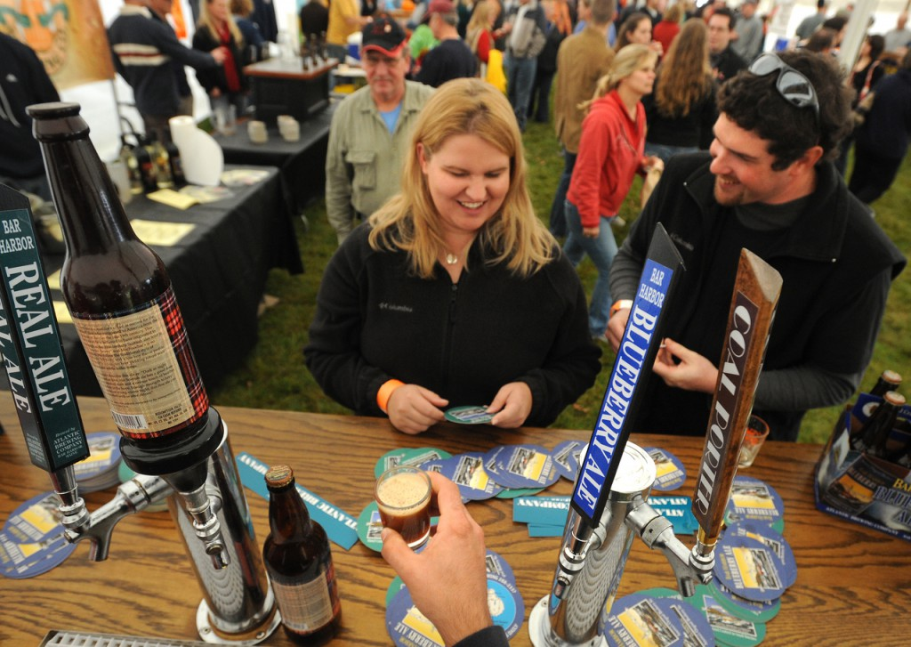 Jessica Wentworth (center) waits to sample some beer with her friend Stephen Genthner of Round Pond at the 14th annual Oktoberfest in Southwest Harbor Saturday.  They drove three hours to visit the festival and were among the hundreds of people who were in beer tent tasting some samples of about 80 brands of Maine made beer and vine. The festival also featured food music and display of work from Maine craftsmen. (Bangor Daily News/Gabor Degre)