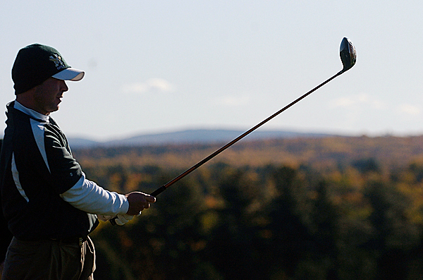 Husson University senior and co-captain John Ellis of Belfast watches his ball on a driving range while practicing before Monday morning's round of the North Atlantic Conference Golf Championship at Penobscot Valley Country Club in Orono. (Bangor Daily News/John Clarke Russ)