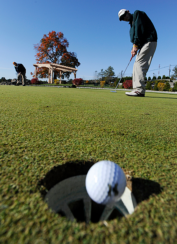 Husson University senior Ben Estabrook of Bangor gets in some putting practice near the club house before Monday morning's round of the North Atlantic Conference Golf Championship at Penobscot Valley Country Club in Orono. (Bangor Daily News/John Clarke Russ)