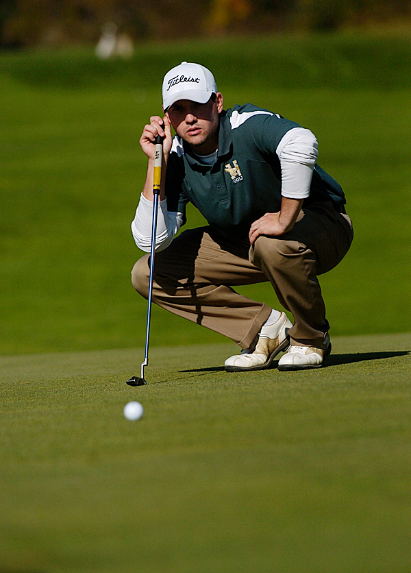 Husson University junior and co-captain Kevin Byrne lines up his putt to hole one during Monday morning's round of the North Atlantic Conference Golf Championship at Penobscot Valley Country Club in Orono. (Bangor Daily News/John Clarke Russ)