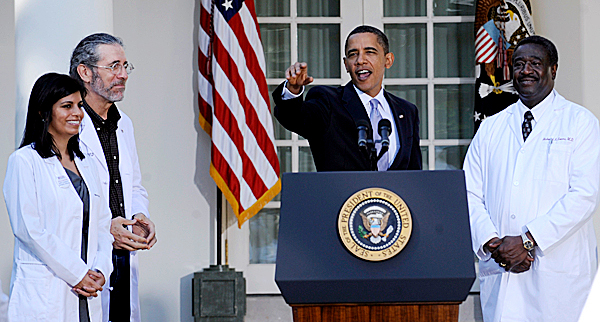 President Barack Obama points to the audience as he speaks in the Rose Garden of the White House in Washington on Monday. From left are  Dr. Mona Mangat of St. Petersburg, Fla.; Dr. Hershey Garner of Fayetteville, Ark.; and Dr. Richard Evans of Dover-Foxcroft. (AP Photo/Susan Walsh)