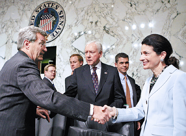 Senate Finance Committee Chairman Sen. Max Baucus, D-Mont., left, shakes hands with committee member Sen. Olympia Snowe, R-Maine, as Sen. Orrin Hatch, R-Utah, is seen at center, Tuesday, Oct. 13, 2009, on Capitol Hill in Washington, after a committee vote regarding the health care reform bill.  (AP Photo/Charles Dharapak)