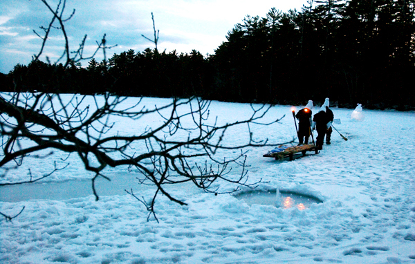 Scene Three of &quotGraupel&quot has two actors dragging a sled with a large frozen object wrapped in burlap led by a third actor sweeping the ice as they pace a sundial of frozen ice.  (BANGOR DAILY NEWS PHOTO BY KEVIN BENNETT)