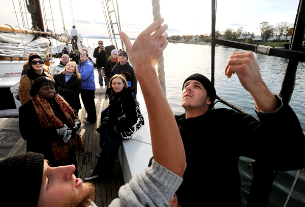 Maine Maritime Academy students Sam Smith (forground left) and Bryan Hammond (right) pull on the main halyard as the crew was taking participants of the third annual Women on the Water conference for a sail aboard the schooner Bowdoin  in the Penobscot Bay Thursday.  The conference held at the Maine maritime Academy in Castine hosts attendees from other maritime academies as well as accomplisehed professionals from maritime related positions. BANGOR DAILY NEWS PHOTO BY GABOR DEGRE