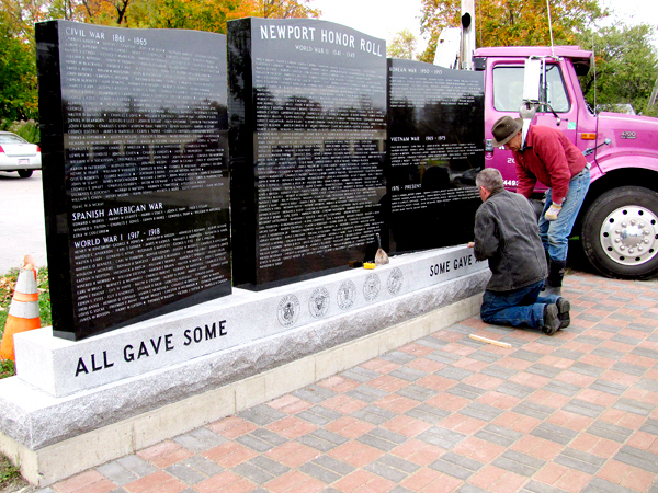 Blain Creighton of Newport Monument (kneeling) and Jim Elias of Elias Monuments of Madison install the last section of a three-piece memorial to honor veterans from Newport who served during wartime.  BANGOR DAILY NEWS PHOTO BY CHRISTOPHER COUSINS