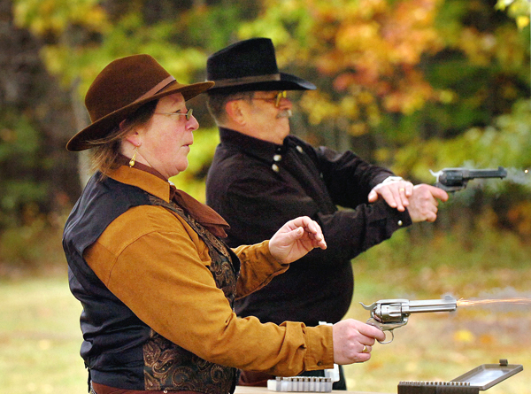 Mary Ann Sheets also known as her cowgirl name &quotDaisy A'Dare&quot of Seal Cove and Ken &quotThe Gold Dust Kid&quot Goldstein of Southwest Harbor practice their fast draw skills at the Blue Hill Rifle & Pistol Club's annual Fall Shoot and Open House on Sunday, Oct. 18, 2009. &quotI tried it at the gun show and I was hooked,&quot said Goldstein of the cowboy fast draw style of shooting. The club was founded in 1946 and has more than 200 members in Hancock County. The club is hosting a cowboy action shoot, complete with costumes and moving between targets, on Saturday, 0ct. 24. (Bangor Daily News/Bridget Brown)