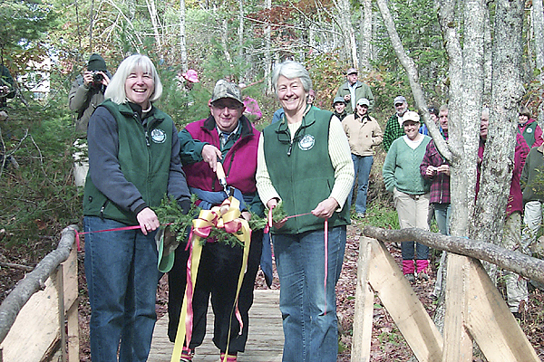 Arizona resident Janet Stetser (center) cuts the branch and ribbon during Saturday's dedication of the 150 acre Stetser Preserve on the Sheepscot River Watershed in Jefferson. Stetser made a vow to preserve the land when she bought the parcels more than 40 years ago. With Stetser are Maureen Hoffman, executive director of the Sheepscot Valley Conservation Association (left) and SVCA president Honor Sage (right). (BANGOR DAILY NEWS PHOTO BY WALTER GRIFFIN)