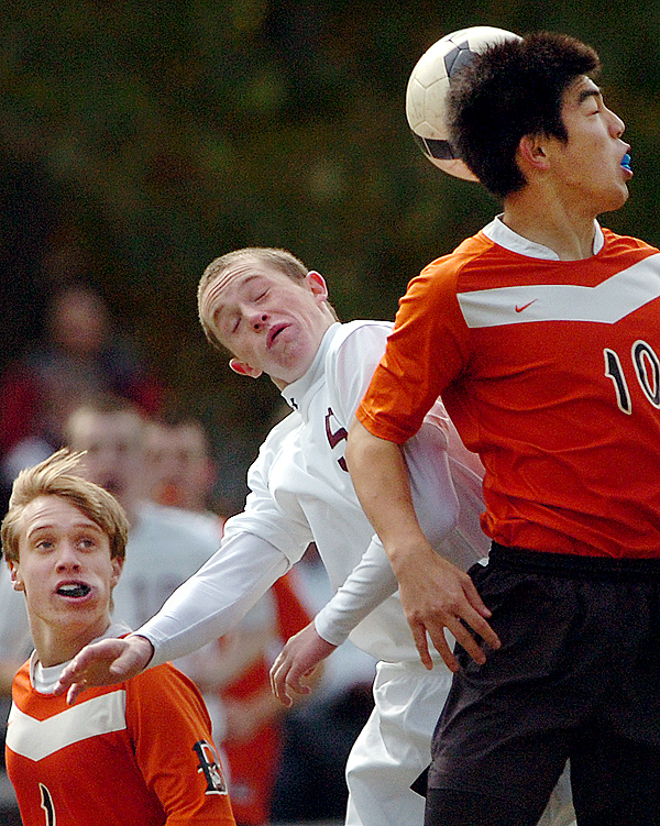 Brewer's Yuhi Sasaki (from right) goes up against Bangor's Luke Hetterman as Brewer's Shawn Williams awaits the outcome in the first half of Saturday's game, Oct. 17, 2009 in Bangor. (Bangor Daily News/Bridget Brown)
