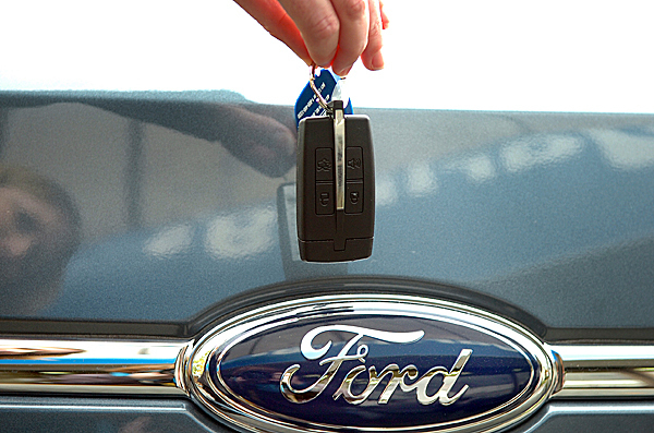 Ford MyKey representative Jennifer Burke holds a MyKey above a 2010 Ford Taurus emblem at Darling's Ford in Bangor on Tuesday, Oct. 20, 2009. The new MyKey feature, which is available for the Taurus model and comes standard in the Ford Focus, allows owners to program a key that limits the vehicle's top speed and audio volume. The feature is especially geared towards parents to give them safety controls for teenage drivers. (Bangor Daily News/Bridget Brown)