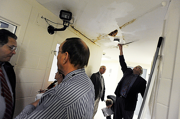 During Tuesday afternoon's tour of the Penobscot County Jail, Penobscot County commissioner Thomas Davis Jr. (District2) peels back a piece of water-damaged ceiling in the maximum-security wing on the jail's second floor. Looking on is fellow Penobscot County commissioner Stephen Stanley (District 3) and in the foreground are Penobscot County Commision Chair Peter Baldacci (District 1) (far left) and  Sheriff Glenn Ross. Sheriff Ross gave local and state officials a tour of the  Penobscot County Jail Tuesday to address jail upgrades and other inmate and staff needs. (Bangor Daily News/John Clarke Russ)