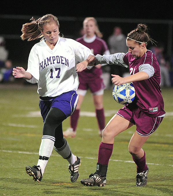 Bangor High School's Ashley Robinson (right) tries to controll the ball as she drives up the field past Hampden Academy's Sarah Lamberton during the first half of the game in Hampden Tuesday evening. (Bangor Daily News/Gabor Degre)