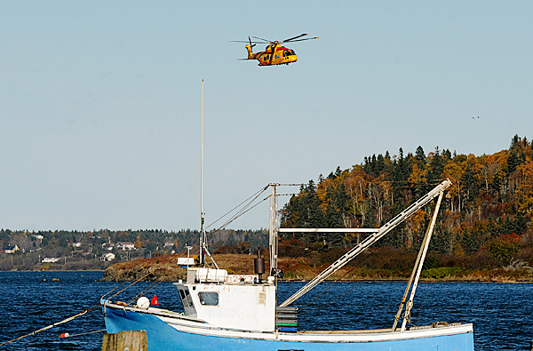 A Canadian Defense Force rescue helicopter searches the waters between Lubec and Campobello Island, New Brunswick  for three Maine fishermen who were on an urchin boat which was reported missing Tuesday evening.  The search, which included the U.S. Coast Guard, Maine Marine Patrol and local fishermen, continued through Wednesday.  The body of one fisherman was found iWednesday afternoon. (Bangor Daily News/Gabor Degre)