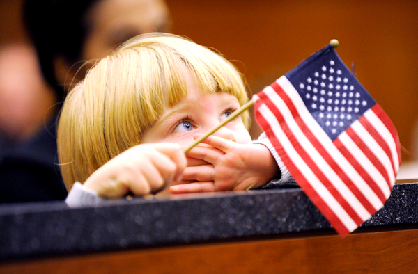 Holding a small flag provided by local Daughters of the  American Revolution, three-year-old Jacob Rae of Hampden watches his father, Christopher Duncombe Rae, shakes hands with U.S. District Court Judge John A. Woodcock Jr., U.S. Bankruptcy Court Chief Judge Louis H. Kornreich (cq) and others during Friday's new citizen swear-in federal court in Bangor. BANGOR DAILY NEWS PHOTO BY JOHN CLARKE RUSS