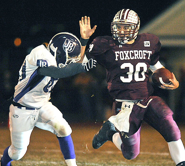 Foxcroft Academy's Ian Champeon, (30), tries to deflect John Bapst's Dan Keefe, (80), in the first half of their game in Dover Foxcroft, Friday, Oct. 23, 2009.