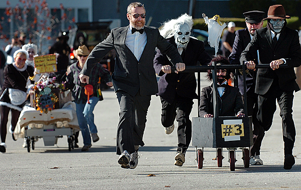 Team three, also known as &quotBlack Magic&quot, including (from left) Rick Chase, David Tweedie, Kim Day (seated) as a &quotdeceased&quot Jonathan Buck, Brian Maguire and Roger Lenor, compete in a coffin race at Bucksport's Ghostport on Sunday, Oct. 25, 2009. The team was undefeated in the event and won the race. Other Ghostport activities Sunday included a parade, chowdah cook-off and pumpkin trebuchet. (Bangor Daily News/Bridget Brown)