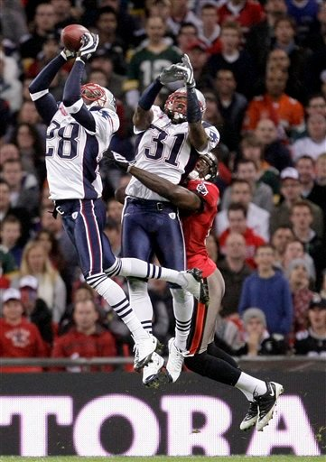 New England Patriots cornerback Darius Butler (28), and safety Brandon Meriweather (31) double team to secure a high ball during an NFL football game against Tampa Bay Buccaneers at Wembley Stadium, London, Sunday Oct. 25, 2009.  (AP Photo/Matt Dunham)