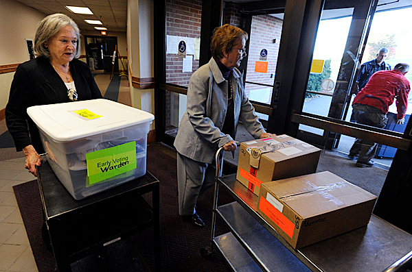 (BANGOR DAILY NEWS PHOTO BY JOHN CLARKE RUSS)    CAPTION    Volunteer Yovanne Stevenson (cq) ,left, of Bangor helps ward clerk Mary Ellen Sullivan, Deputy Registrar of Voters Mike Gleason and Bangor Police Sgt. Paul Edwards deliver voting equipment and paperwork just before the polls opened Monday morning at the Bangor Civic Center. The Bangor Civic Center was one of several sites across the state participating in Maine's Early Voting Pilot Program. (Bangor Daily News/John Clarke Russ)
