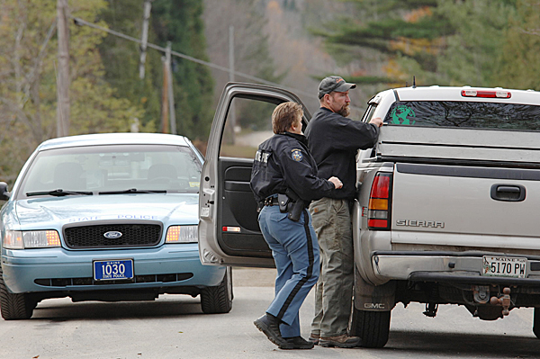 At a roadblock off Route 222 in Newport Tuesday morning, October 27, 2009, Maine State Police Trooper Brenda Coolen, center, checks the body and tool box of a pick up truck as an unidentified man turned onto the Rutland Road.  Police were looking all of Tuesday for a Newport man who allegedly shot and killed his father Monday night.(Bangor Daily News photo by Scott Haskell)