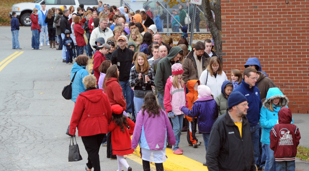 People stand in line outside the Bangor Civic Center Wedesday morning to get their children vaccinated for H1N1 and seasonal influenza. Some waited for as much as 2-3 hours during a mass vaccination.  About 4000 doses of H1N1 and 2900 doses of seasonal influenza vaccine were available in Bangor. (Bangor Daily News/Gabor Degre)