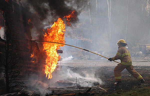 Volunteer firefighter Tom Krapf uses a grappling hook to turn over some burning embers in a fire that totally destroyed a log cabin home at 66 Rocky Road in Lakeville on Wednesday. Firefighters were handicapped in fighting the blaze by a lack of water. (Bangor Daily News/Nick Sambides Jr.)