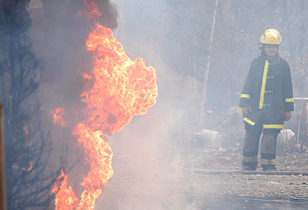 A Lakeville volunteer firefighter can only watch as a lack of water impeded the department?s ability to stop a fire that totally destroyed a log cabin home at 66 Rocky Road in Lakeville on Wednesday. (Bangor Daily News/Nick Sambides Jr.)