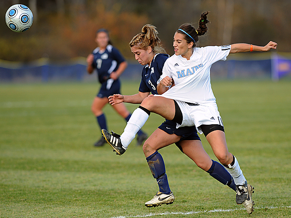 The University of Maine's Stephanie Frenette-Blais (right) kicks the ball away from the University of New Hamphire's Stephanie Gilkenson during the America East quarterfinal game in Orono Thursday.  Maine won the game 2-1 in overtime. (Bangor Daily News/Gabor Degre)