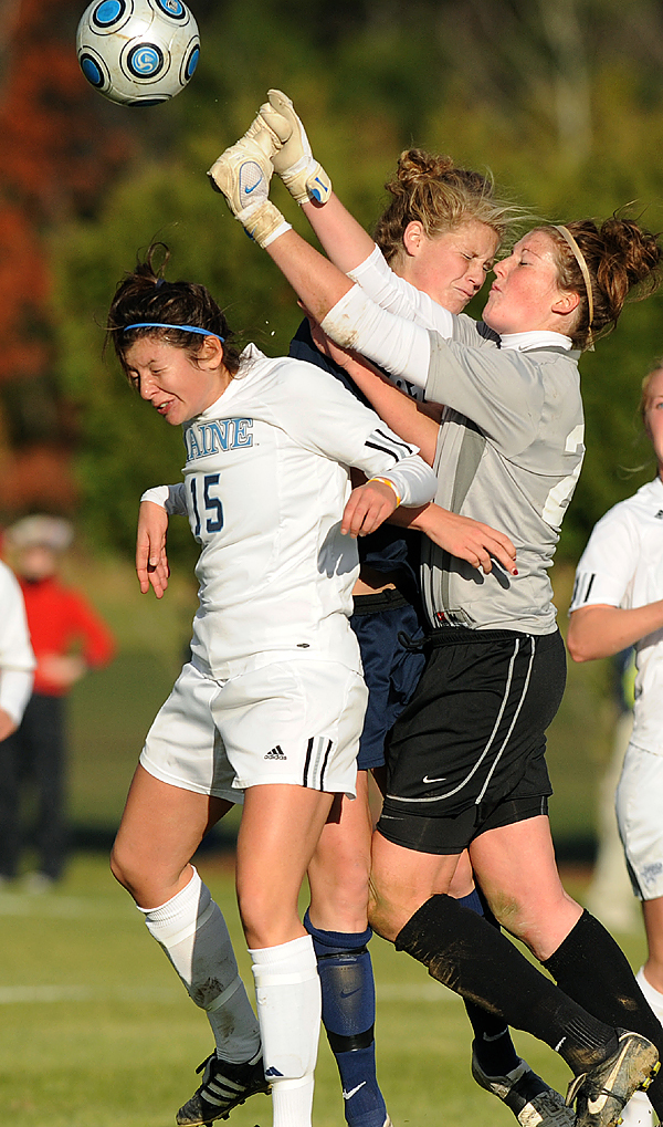 University of New Hamphire's goal keeper Ally Yost (right) hits the ball away as her teammate Kelley Spencer (center) and the University of Maine's Danielle DelNero go up for a header during the America East quarterfinal game in Orono Thursday.  Maine won the game 2-1 in overtime. (Bangor Daily News/Gabor Degre)
