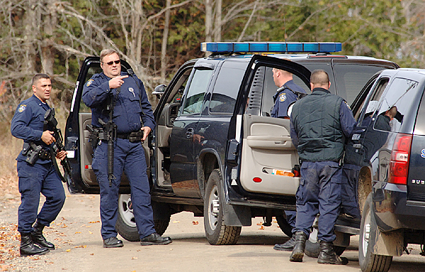 CAPTION Acting on a tip that a man was seen nearby, State Police search a property and buildings on the Pratt Road in Newport.  A massive manhunt for Perley Goodrich, Jr. continued all of Tuesday after he allegedly shot and killed his father on the Rutland Road in Newport Monday night.  (Bangor Daily News photo by Scott Haskell)   (WEB EDITION PHOTO)