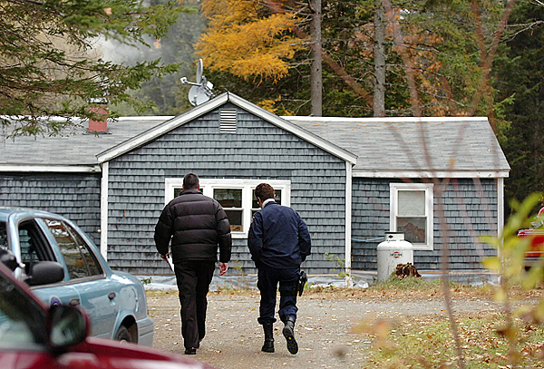 CAPTION  Maine State Police officials including Lt. Jackie Theriault (right) continue their investigation at 146 Rutland Road in Newport on Tuesday, Oct. 27, 2009, where a shooting occured late Monday night. Police identified the victim as Perley Goodrich Sr., 76, and are still searching for his son Perley Goodrich Jr., who resided with his two parents, for questioning. Police officials say Goodrich is considered to be armed and dangerous and is asking anyone who has contact with him to call State Police in Orono. (Bangor Daily News/Bridget Brown)    (WEB EDITION PHOTO)