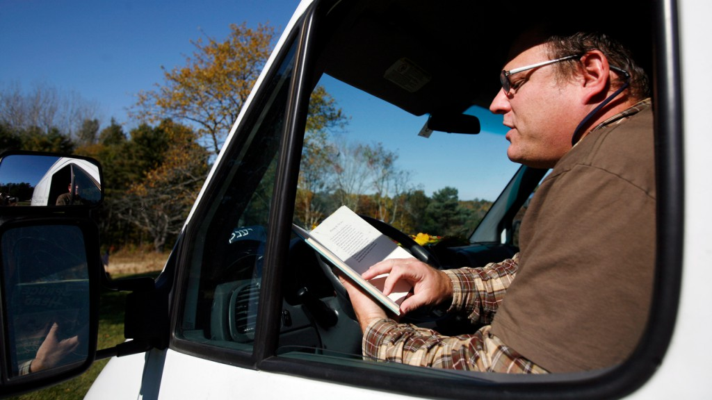 Walter Skold, founder of the Dead Poets Society of America, reads a poem while sitting in his van at a graveyard in Cundys Harbor, Maine.