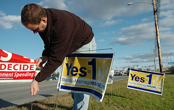 Yes on 1 volunteer Josh Delano of Orrington pauses to fix a campaign sign Sunday, Nov. 1, 2009 after lining Wilson Street in Brewer with Yes on 1 signs for the third time because of them disappearing or being dismantled. &quotI'm just gonna put up yes signs next to all the no signs and we'll call it equal,&quot Delano said. (Bangor Daily News/Bridget Brown)