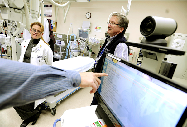 In Eastern Maine Medical Center's trauma rooms, pediatric internist George Payne, M.D (hand on left), trauma surgeon Joan Pellegrini, M.D. (left) and trauma coordinator Bjorn Pret, R.N. discuss EMMC's teletrauma video conferencing system which will provide remote access communication with 15 other community hospitals by the end of this year. (Bangor Daily News/John Clarke Russ)