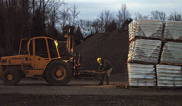 A worker at the Scotts Miracle-Gro Co. plant in Medway straightens a pallet on a forklift at dusk on Monday. The plant will expand its capacity by adding a third production line that will help the company produce its NatureScapes mulch and Miracle-Gro potting mix, company officials said. Buy Photo