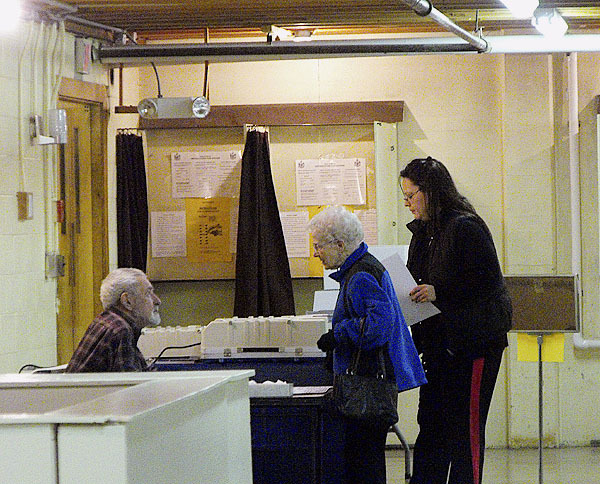 Houlton residents turn in their ballots after voting late Tuesday afternoon at the Gentle Memorial Building in Houlton. Town Clerks across Aroostook County noted that a steady stream of voters flowed into polling places to cast ballots on a number of hot-button issues. Voters also were choosing representatives to serve on municipal and school board seats. Buy Photo
