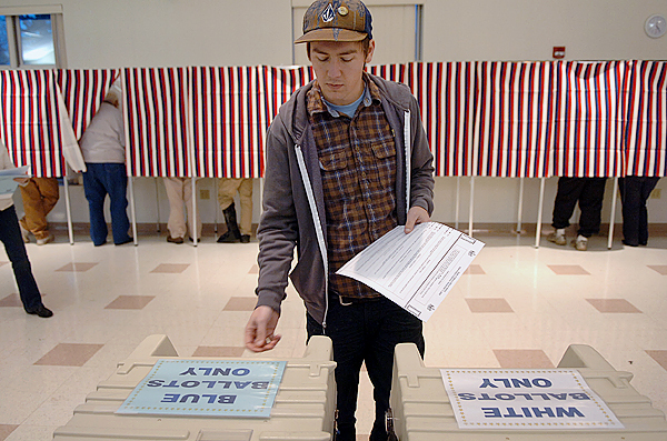 Jeremy Yehle casts his vote at the Hampden Municipal Building on Tuesday. According to town clerk Denise Hodsdon, by about 4:30 p.m., more than 2500 residents had cast their votes, either in person or by absentee ballot, of Hampden's 5800 registered voters. Buy Photo