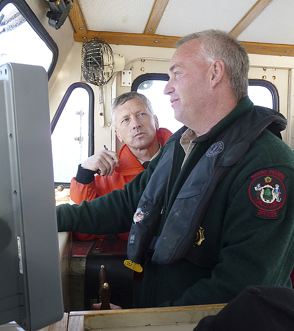 Department of Marine Resources Lt. Alan Talbot (left) talks with DMR Specialist Russell Wright about the ongoing search in Cobscook Bay. (Bangor Daily News/Sharon Kiley Mack)
