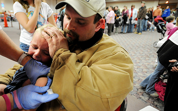 (BANGOR DAILY NEWS PHOTO BY GABOR DEGRE)  CAPTION  Jay Hughes of Brewer holds his three-year-old son Logan while he was getting vaccinated for H1N1 at the Bangor Civic Center Wednesday afternoon Nov. 4, 2009.  This was the second mass vaccination for school-age children in the Bangor area in as many weeks.  1500 doses of the H1N1 vaccine were used before 1p.m from the available 2300 doses.  Most people said that they were in line between 30 to 45 minutes, not nearly as long as during the first mass vaccination last week. Logan's sisters Megan, 7, and Katie, 12, also were vaccinated.  (Bangor Daily news/Gabor Degre)