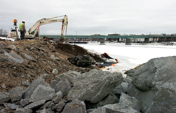 Workers grade the slope leading to the Penobscot River on Friday as part of Brewer's shorefront stabilization project. Because of changing water levels, some of the work required for the project can be done only at low tide.  (BANGOR DAILY NEWS PHOTO BY KATE COLLINS)