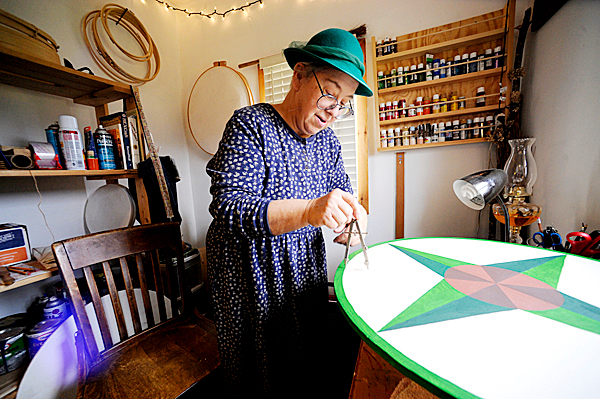 Artist J.J. Starwalker works on one of her Dutch hex signs in her home studio in West Corinth October 29, 2009. In keeping with hex sign making tradition, she wears a hat to &quotcover thy head in the presence of the divinity, &quot she said.  BANGOR DAILY NEWS PHOTO BY JOHN CLARKE RUSS